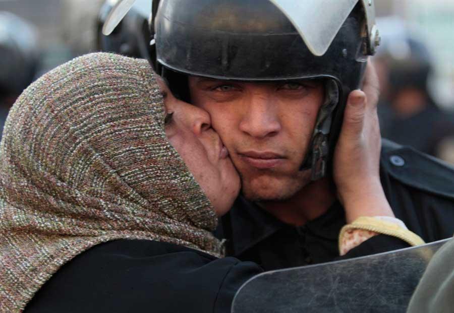 mujer-egipcia-besa-a-un-policia-durante-la-revolucion-del-gobierno-de-mubarak-egipto-2011